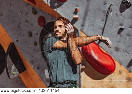 Portrait Of Caucasian Man Professional Rock Climber Warms-up At Front Of Climbing Wall At Training C