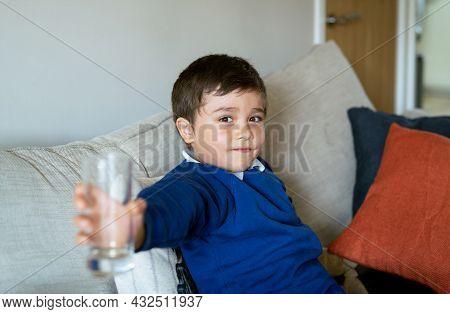 Happy School Kid Holding Clear Glass, Portrait Mixed Race Child Boy Sitting On Sofa Showing Empty Gl