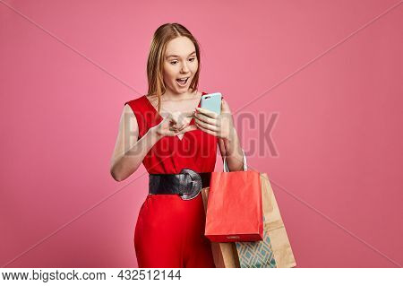 Studio Shot Of Happy Woman Shopper Holding Shopping Bags Using Mobile Apps For Online Shopping On A