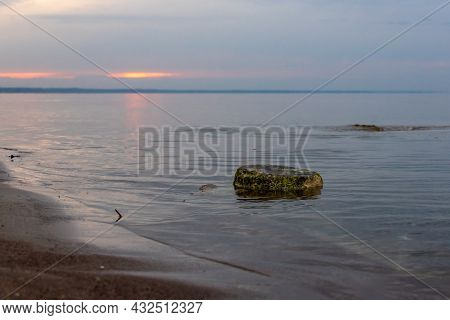 Mossy Stone And Sunset Over The Sea After Rainy Day. Dark Sunset Reflecting In Calm Smooth Sea At Kl