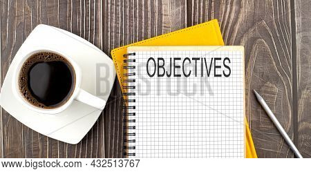 Objectives Text On The Notebook With Coffee On The Wooden Background