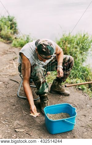 A Young Fisherman Catches Fish On A Lake Or River, Prepares Tackle And Bait. Hobbies, Weekends, Fish