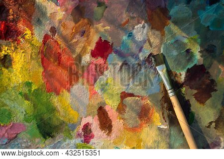 An Artist's Palette With An Oil Paint Brush Close-up. Blurry Multicolored Background. The Artist's P