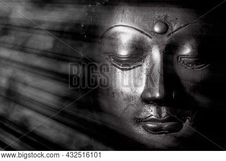 Zen Buddhism And Spiritual Enlightenment. Mindful Monochrome Buddha Face Illuminated By Mystical Hea