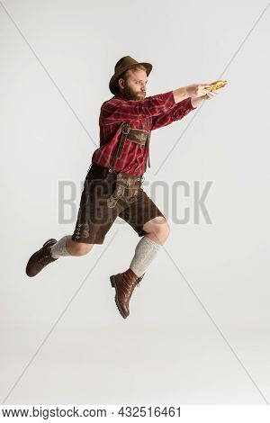 Full-length Portrait Of Bearded Man In Hat And Traditional Bavarian Costume Jumping High Isolated Ov