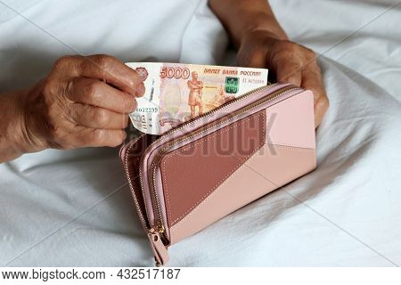 Elderly Woman Takes Out Russian Rubles From Her Wallet Sitting In Bed, Wrinkled Female Hands Closeup