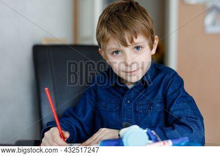 Hard-working School Kid Boy Making Homework During Quarantine Time From Corona Pandemic Disease. Chi