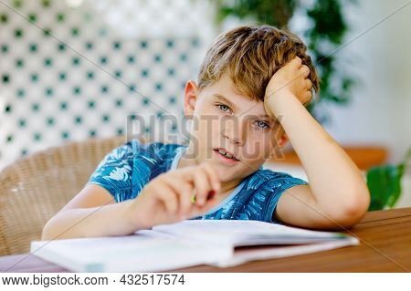Hard-working Happy School Kid Boy Making Homework During Quarantine Time From Corona Pandemic Diseas