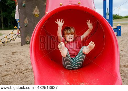 Little Preschool Girl Playing On Outdoor Playground. Happy Toddler Child Climbing And Having Fun Wit