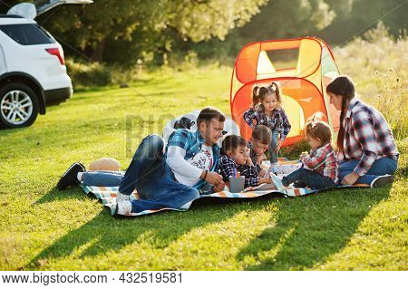 Family Spending Time Together. Four Kids And Parents Outdoor In Picnic Blanket. Large Family In Chec