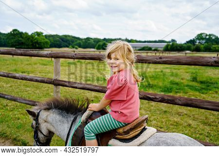 Little Preschool Girl Riding A Pony On A Farm. Happy Lovely Child Practicing Horseback Riding. Outdo