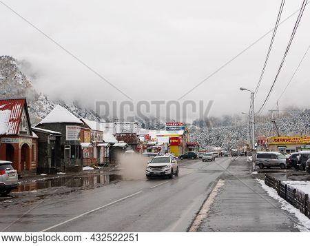 Chemal, Altai Republic, Russia - 15 October 2020: Russian Rural Village Chemal In The Snow. Cars Dri