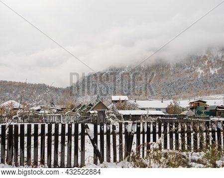 Russian Rural Village Chemal In The Snow. Behind A Wooden Fence There Are Houses Covered With Snow A