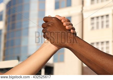Men Clasping Hands On City Street, Closeup