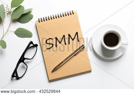 Notebook With Abbreviation Smm, Cup Of Coffee And Glasses On White Background, Flat Lay. Social Medi