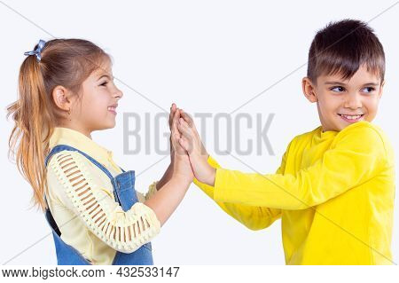Two Adorable Kids Touching With Palms Holding Together And Boy Is Hesitates Girl, Turned His Head Le