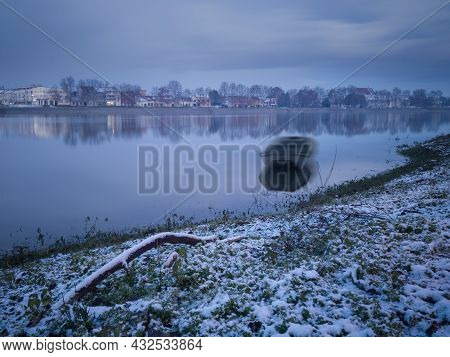 Moored Boat In Water In Long Exposure In Winter During Dusk, Calm Reflecting Water And Snow Covered