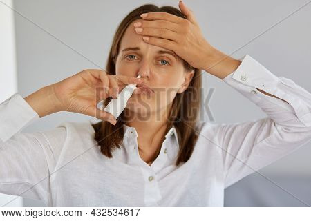 Closeup Of Ill Young Adult Woman Using Nasal Spray, Suffering From Runny Nose And Terrible Headache,