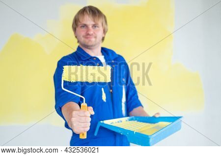 Man Painting Wall In Yellow Color With Roller. Renovation, Repair And Redecoration Concept. Selectiv