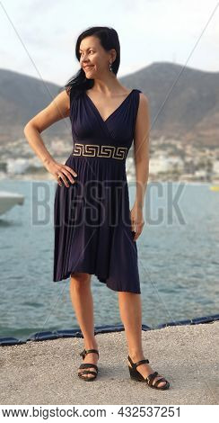 Happy Young Woman On The Pier In The Morning In The Soft Rays Of The Sun On Crete In Greece