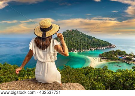 Woman Traveler Wearing White Dress And Straw Hat At Nang Yuan Island, Koh Tao, Thailand In A Summer
