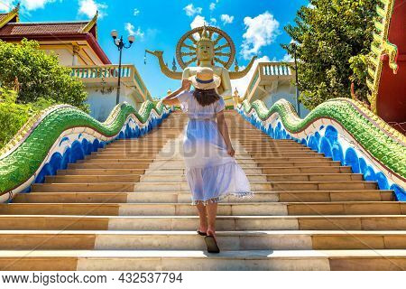 Woman Traveler Wearing Blue Dress And Straw Hat At Big Buddha On Koh Samui, Thailand In A Summer Day