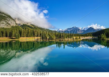 Blue Sky Reflecting Over Cascade Ponds In Banff