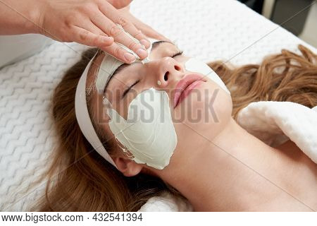 Cosmetologist Applying Rejuvenating Facial Mask On A Female Face In Beauty Salon. Facial Treatment C