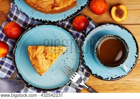 Homemade Pie With Nectarines And Cup Of Tea On Wooden Table. Top View.