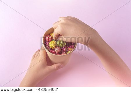 Child Hands Holding Box With Colorful Rainbow Caramel Candy Popcorn On Pink Background. Cinema Snack