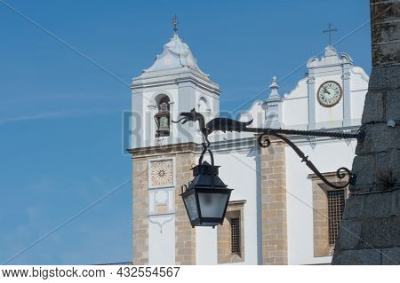 Close Up Of A Street Lamp With A Dragon Sculpture. In The Background Church At Giraldo Square, Evora
