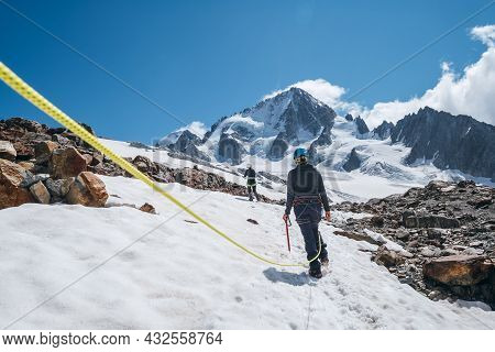 Two Females Rope Team Members On Acclimatization Day Dressed In Mountaineering Clothes Walking In Cr