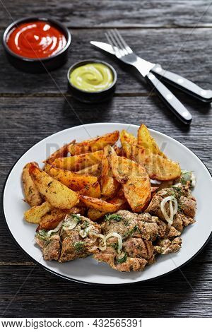 Grilled Pork Shoulder Steaks With Roasted Potato Wedges Seasoning With Paprika And Dill On A Plate O