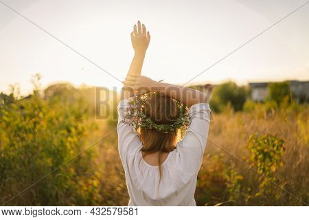 Summer Lifestyle Portrait Of Beautiful Young Woman In A Wreath Of Wild Flowers. Standing Back In The
