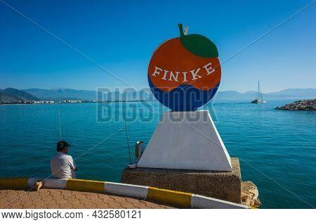 Finike, Turkey - 26 October, 2019: Man fishing in shadow of decorative orange like sign of Finike city on waterfront Turkish Mediterranean sea, province of Antalya
