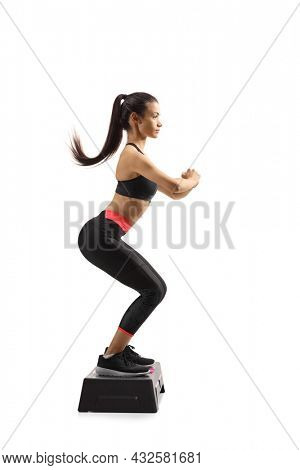 Full length profile shot of a young woman exercising step aerobic isolated on white background
