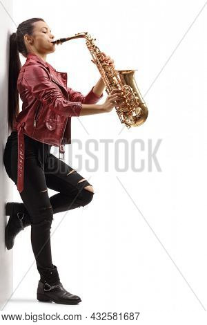 Full length profile shot of a young female in a leather jacket playing a saxophone and leaning on a wall isolated on white background
