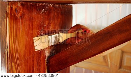 Varnishing The Details Of An Old Wooden Bench With A Narrow Brush, Renovation Of Dilapidated Furnitu