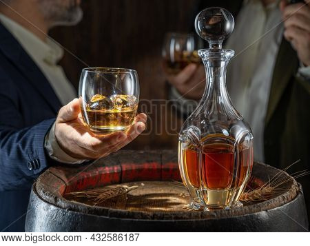 Whisky tasting. Man sits in front of a barrel with a decanter and a glass of whiskey.