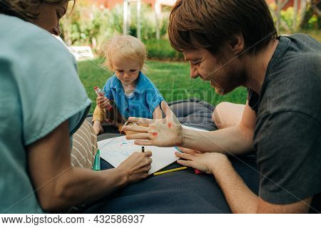Cheerful Man Showing Palm With Heart Stamp. Mid Adult Parents Resting With Toddler Daughter On Mattr