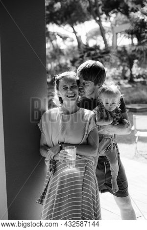 Affectionate Husband Holding Kid And Kissing Wife Outdoors, Woman Standing With Glass Of Water And L