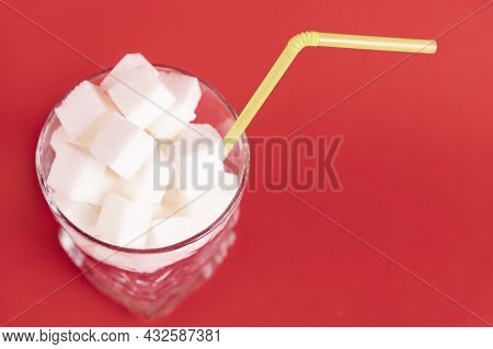 A Glass Of White Glass With A Straw Filled With White Cubes Of Refined Sugar On A Red Background. Co