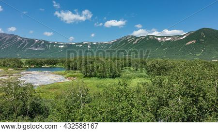 The Caldera Of An Extinct Volcano Is Surrounded By A Mountain Range.  In The Valley There Is A Blue