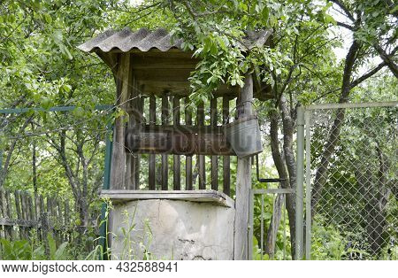 Old Well With Iron Bucket On Long Forged Chain For Clean Drinking Water