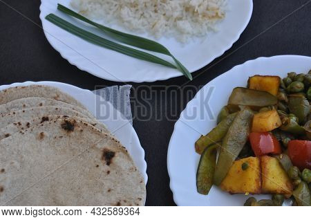 Closeup Of Matar Paneer Veg, Roti (indian Bread) And Rice On White Plate Over Black Background