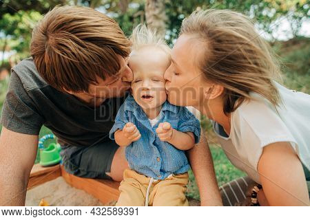 Happy Parents Kissing Displeased Little Girl. Portrait Of Cute Toddler Child Squinting Off Her Paren