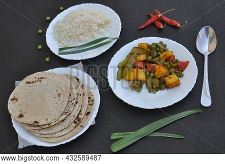 Rice, Matar Paneer Mix Veg And Roti (indian Bread) On White Plate Over Black Background