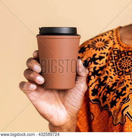 Indian man holding a tumbler