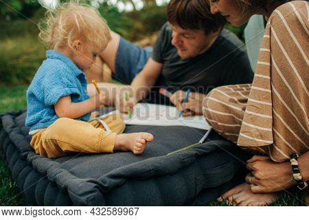 Cute Little Child Painting With Parents In Park. Mid Adult Parents Sitting On Mattress And Playing W