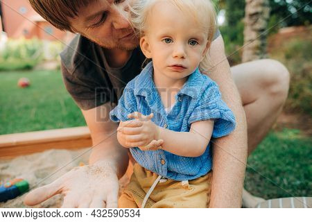 Portrait Of Happy Father With Child In Sandbox. Mid Adult Man Sitting With Toddler Daughter In Sandp